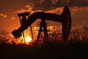 Silhouettes Prints - Oil rig pump jack silhouetted by setting sun Print by Mark Duffy