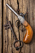 Guns Photos - Old pistol and skeleton key by Garry Gay