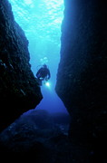 Oceanic View Prints - One scuba diver shines an underwater light while swimming through a cave Print by Sami Sarkis
