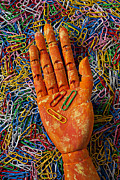 Office Photo Acrylic Prints - Orange wooden hand holding paperclips Acrylic Print by Garry Gay