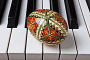 Pianos Prints - Painted Easter egg on piano keys Print by Garry Gay