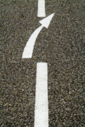 Locations Prints - Painted white arrow sign in the dividing line on the road Print by Sami Sarkis