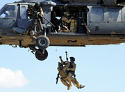 Baghdad Posters - Pararescuemen Are Hoisted Into An Hh-60 Poster by Stocktrek Images