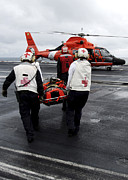Flight Deck Posters - Personnel Carry An Injured Sailor Poster by Stocktrek Images