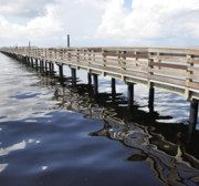 Water Reflections Photos - Pier Reflections by Sandy Poore