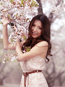 Asian Woman Framed Prints - Portrait of a Young Smiling Woman Standing at a Cherry Tree Framed Print by Oleksiy Maksymenko
