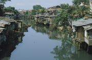 Poor People Photo Prints - Ramshackle Houses Line A Canal Print by Tim Laman