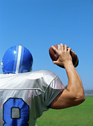 Waist Up Photos - Rear View Of A Football Player Throwing A Football by Stockbyte