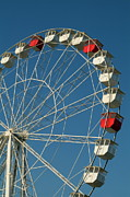 Carriages Posters - Red and white empty carriages on a ferris wheel at an amusement park Poster by Sami Sarkis