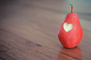 Eating Photo Framed Prints - Red Pear With Heart Shape Bit Framed Print by Danielle Donders - Mothership Photography
