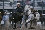 Rodeos Prints - Ricky Huddleston Drops Off His Horse Print by Bobby Model