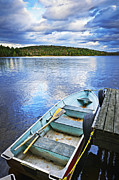 Calm Water Reflection Posters - Rowboat docked on lake Poster by Elena Elisseeva