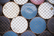 Stored Metal Prints - Rows of Stacked Barrels Behind a Fence Metal Print by Paul Edmondson