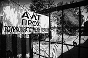 Turkish Photos - rusty fence and razor wire in UN buffer zone in the green line dividing north south cyprus by Joe Fox