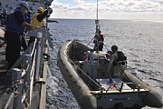 Inflatable Photos - Sailors Lift A Rigid-hull Inflatable by Stocktrek Images