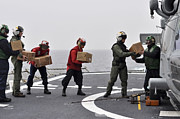 Uss Ronald Reagan Prints - Sailors Load Boxes Of Food Onto An Print by Stocktrek Images