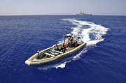 Inflatable Photos - Sailors Transit An Inflatable Boat by Stocktrek Images