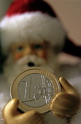 Coins Framed Prints - Santa Claus doll holding out a euro coin Framed Print by Sami Sarkis