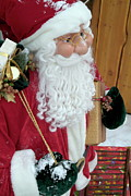 Father Christmas Prints - Santa Claus toy standing next to Christmas presents Print by Sami Sarkis