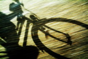 Sami Sarkis Posters - Shadow of a person riding a bicycle Poster by Sami Sarkis
