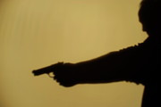 Authority Photos - Shadow of man pointing gun by Sami Sarkis