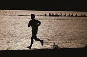 Jogging Posters - Silhouette Of A Jogger Next To Water Poster by Roy Gumpel