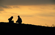 Bonding Metal Prints - Silhouette of a squatting couple at sunset Metal Print by Sami Sarkis