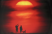 Pet Owner Prints - Silhouette Of Couple With Dog, Man Aiming, Sunset Print by David De Lossy