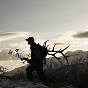 Mountain In Snow Posters - Silhouette Of Hunter Hiking With Elk Antlers Poster by Mike Kemp Images