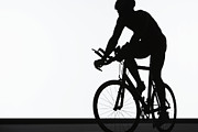 Triathlon Prints - Silhouette Of Triathlete Riding On Bicycle Print by Paul Taylor