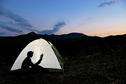 Getting Away Prints - Silhouette of woman reading book in illuminated tent Print by Sami Sarkis
