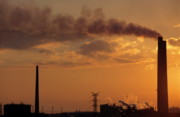 Polluting Prints - Silhouetted smoking chimney at sunset Print by Sami Sarkis