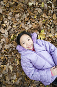 Human Nature Posters - Smiling Girl Lying On Autumn Leaves Poster by Ian Boddy
