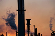 Smokestacks Posters - Smoking chimneys of a petroleum refinery at sunset Poster by Sami Sarkis