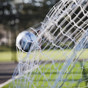 Soccer Ball Framed Prints - Soccer Ball in Goal Netting Framed Print by Jetta Productions, Inc