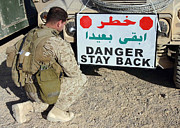 Kneeling Prints - Soldier Secures A Warning Sign Print by Stocktrek Images