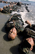Physical Fitness Posters - Soldiers In Training Lay In The Surf Poster by Stocktrek Images