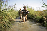 Trudging Posters - Soldiers Patrol Through An Irrigation Poster by Stocktrek Images