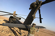 Uh-60 Black Hawk Prints - Soldiers Prepare A Uh-60 Black Hawk Print by Stocktrek Images