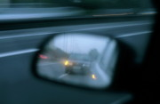 Rear View Mirror Prints - Speeding car on a highway reflected in the rear view mirror of another car Print by Sami Sarkis