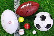 Soccer Balls Framed Prints - Sports balls on grass from above. Framed Print by Richard Thomas