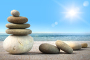 Wellbeing Prints - Stack of spa rocks on wood against blue sky Print by Sandra Cunningham