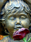 Little Boy Prints - Statue of Child Smelling Red Rose Print by Jeff Lowe