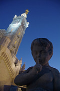 Silence Of Night Prints - Stone statue of a cherub with view of the bell tower of Notre Dame de la Garde in Marseille Print by Sami Sarkis