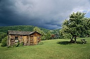 Lawns Fields Framed Prints - Storm Clouds Form Above A Log Cabin Framed Print by Raymond Gehman