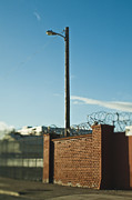 Guarded Framed Prints - Street Lamp Behind Brick Wall With Concertina Wire Framed Print by Eddy Joaquim