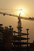 Tower Crane Framed Prints - Sun Shining Behind a Construction Crane Framed Print by Shannon Fagan