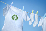 White Prints - T-shirt with recycle logo drying on clothesline on a  summer day Print by Sandra Cunningham