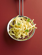 Cilantro Prints - Tagliatelle In Colander On Red Background Print by Westend61