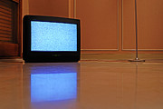 Reflective Art - Television displaying static reflected in floor by Sami Sarkis